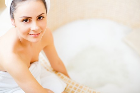 Lady in white towel preparing for her hot bath at home. Stock Photo