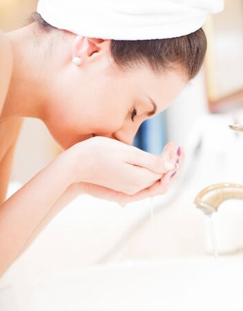 Lady in white towel hydrating her face.