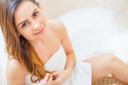 Pretty lady in the bathroom in white towel preparing for a hot bath. Stock Photo