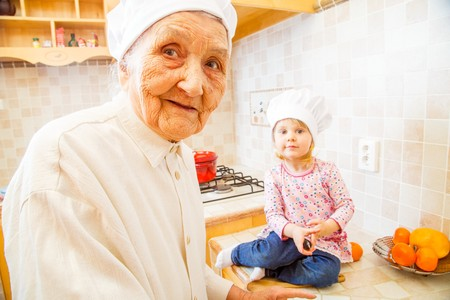 companion: Little girl keeping companion for elderly lady in the kitchen. Stock Photo