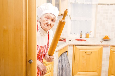 Funny elderly lady hiding in the kitchen with rolling pin in hand.