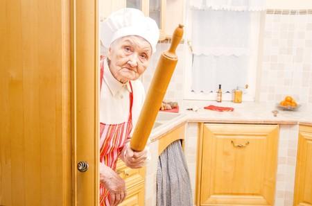 Divertente anziana signora si nasconde in cucina con il mattarello in mano. Archivio Fotografico