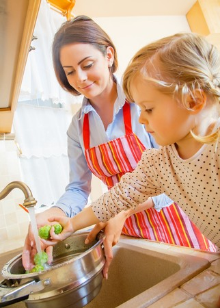 motherly: Beautiful mother with cute little daughter preparing food in the kitchen.