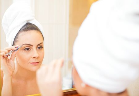 tweezing: Beautiful lady picking her eyebrows in the mirror. Stock Photo