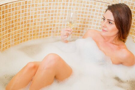 deserved: Lady enjoying her well deserved relaxation at home in the bathtub with bubbles.