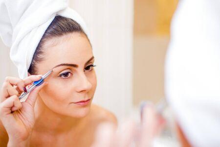 pinzas: Mujer bonita que la depilación con pinzas las cejas en el espejo.