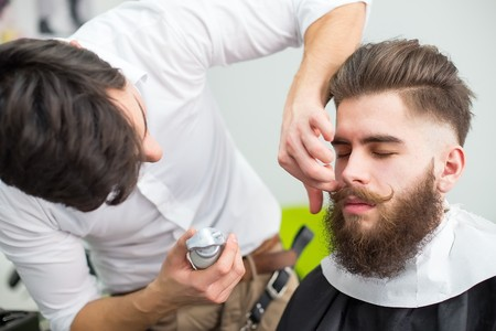 styler: Hipster guy getting his mustache ready for the shooting. Stock Photo
