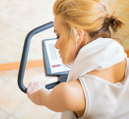 revitalizing: Beautiful woman doing her daily fitness excercises on stationary bycicle at the gym.