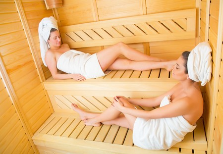 deserved: Female couple enjoying their well deserved sauna moments together.