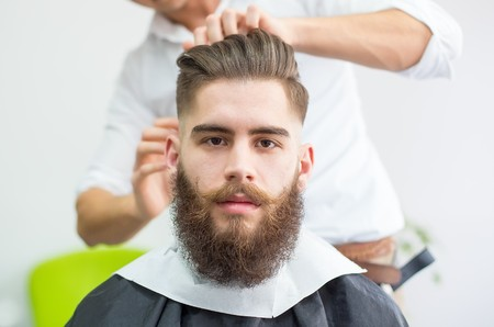 Hipster guy getting ready for the shooting at the barber. Stock Photo