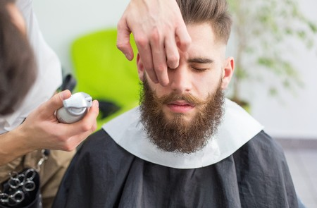 styler: Hipster guy getting ready for the shooting at the barber.
