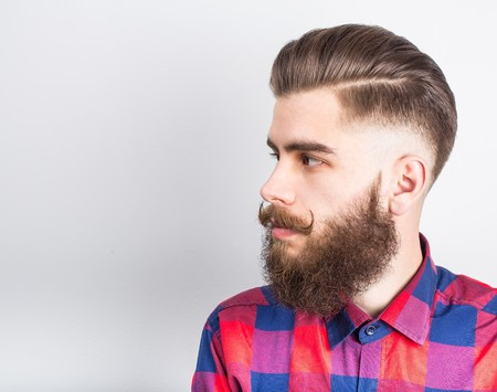 chequer: Portait of a handsome hipster guy over white background.