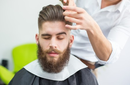 twirl: Hipster guy getting his hair done for the shooting. Stock Photo