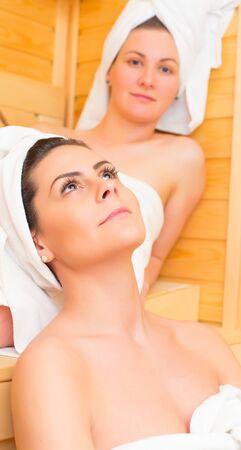 gay girl: Two beautiful women at the sauna relaxing.