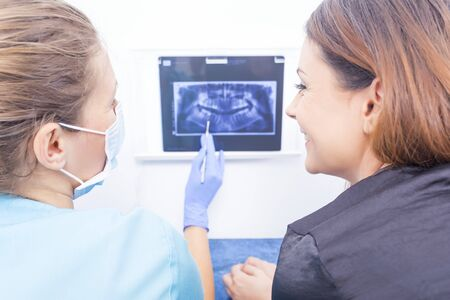 x ray image: Satisfied patient smiling to doctor who explains the panoramic x ray image.