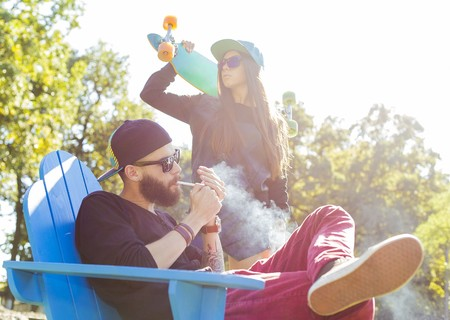taking a break: Hipster couple taking a break and smoking on bench. Stock Photo