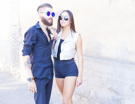 men and women: Two elegant hipster people in sunglasses posing. Stock Photo
