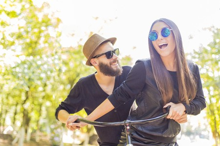 Laughing hipster couple hanging out together and enjoying it entirely.