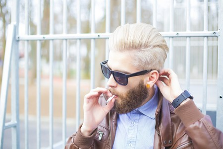 habbit: Hipster man smoking in a forbidden area in public. Stock Photo