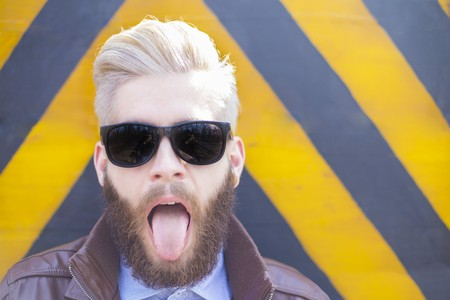 beard man: Blond hipster guy with beard sticking his tongue out.