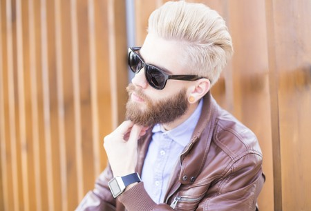 expressionless: Portrait of a dyed blond hipster guy with  black sunglasses.