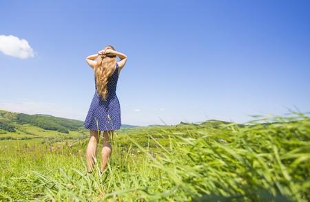 persona caminando: chica rubia en el prado para respirar aire fresco.