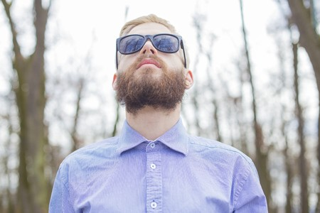 expressionless: Hipster guy showing how to wear beard, hair and glasses with genuine style.