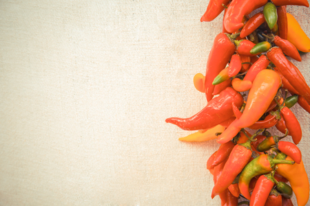 spicey: Colorful chilly peppers on an empty kitchen table. Stock Photo