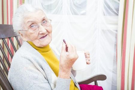 vieille dame malade de prendre ses médicaments avec une tasse d'eau.