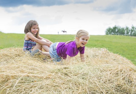 cute little girls playing in the hay