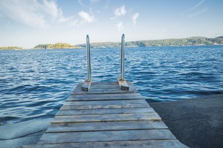 muelle de madera en el agua azul profundo
