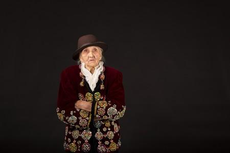 Old woman wearing a vermilion velvet jacket