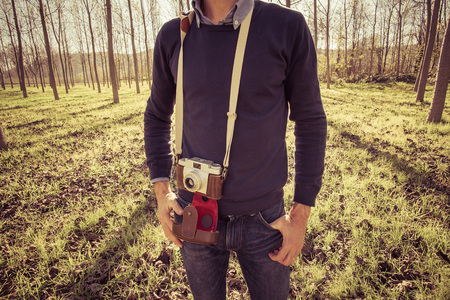 photojournalist: Man in a wood with a vintage photo camera