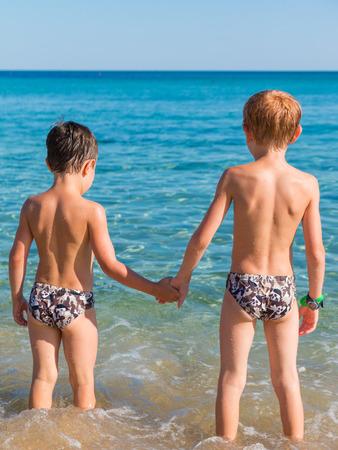 niño sin camisa: Dos niños de la mano en la playa en frente del mar Foto de archivo