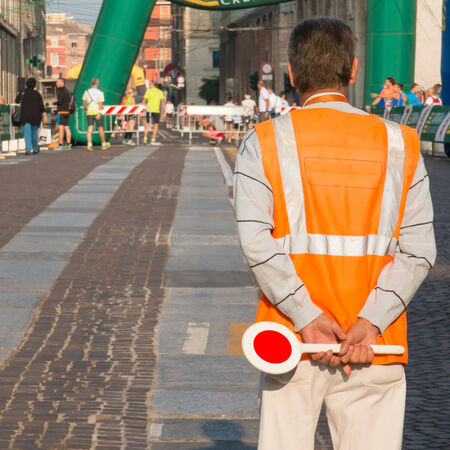 traffic warden: traffic warden with paddle standing in street before city marathon