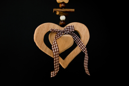 Wooden heart on a rope with wooden balls, a bow in the middle, squared ribbon photo
