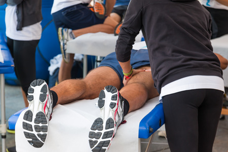 athletes relaxation massage before sport event, marathon muscles massage Editoriali