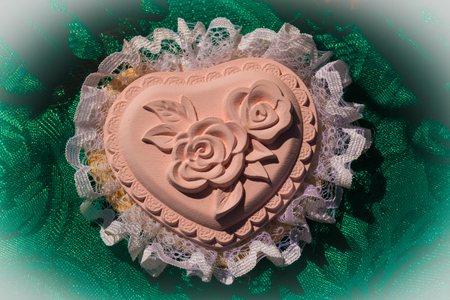 plaster pink heart box with lace and high relief roses on green tablecloth background photo