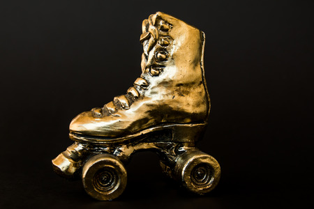 golden roller skate with high heel isolated against black background