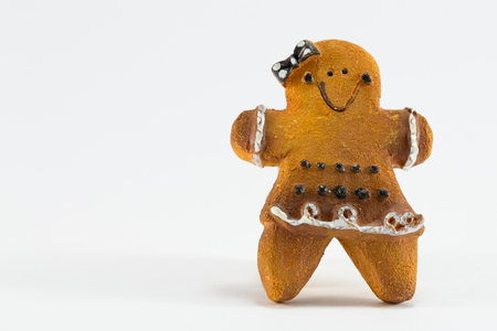 A Christmas woman cookie statuette with bow and skirt on white background photo
