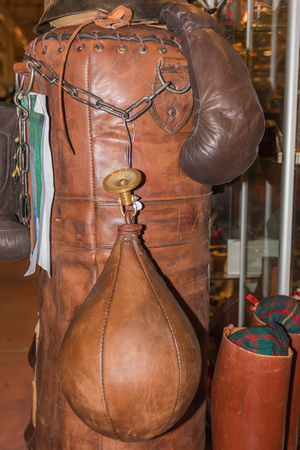Old boxing gloves and leather punching sack photo