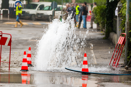 water hole: road spurt water beside traffic cones