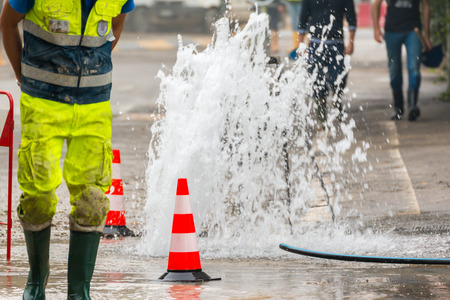 people street: road spurt water beside traffic cones