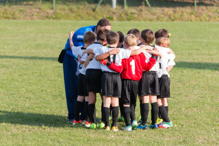 Little league players in huddle, teamwork strategy to win together the match