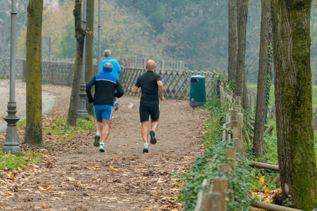 leg muscle fiber: Men jogging in park in autumn. Health and fitness