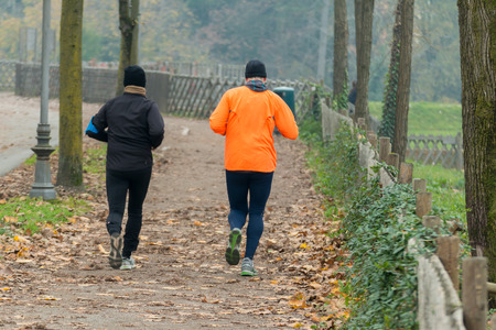 leg muscle fiber: Two men jogging in park in autumn. Health and fitness