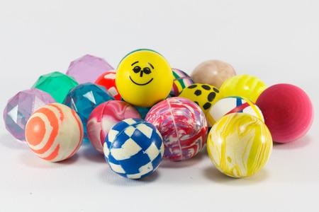 Gruppe von bunten springenden Gummikugeln auf weißem Hintergrund