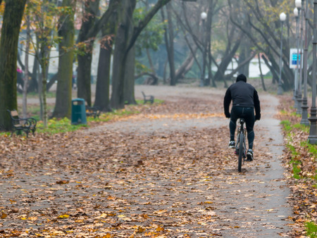 leg muscle fiber: Man riding bike in park in autumn. Health and fitness