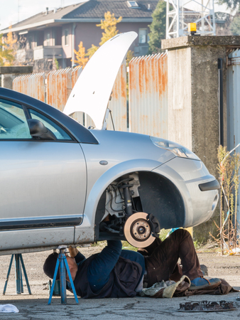 Male mechanic working on a car
