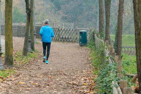leg muscle fiber: Elderly man jogging in park in autumn. Health and fitness